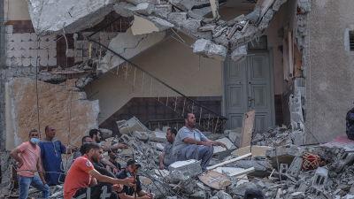 Palestinier som letade efter överlevande vilade på husruiner i Gaza City på söndag morgon.
