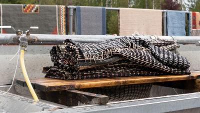 En ihoprullad våt svartvit trasmatta vid tvättställ.