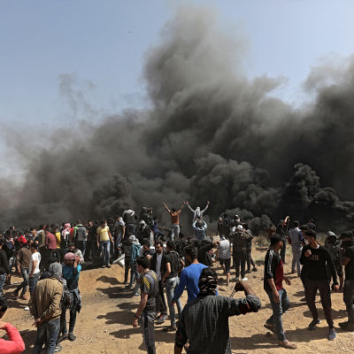Palestinska demonstranter står bakom rökridåer nära gränsen mellan Israel och Gaza.
