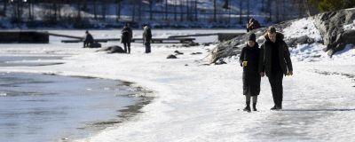 En man och en kvinna promenerar i solskenet på en isig strand.