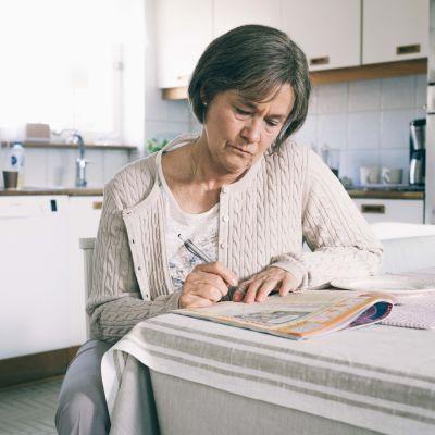Britt-Marie sitter vid köksbordet och skriver en av sina listor.