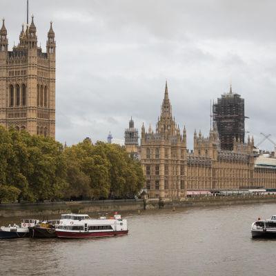 Ljusbruna byggnader i klassisk stil med mycket utsmyckningar vid en flod på vilken det trafikerar båtar. Byggnaden har tinnar och torn, varav ett är högre än de andra.