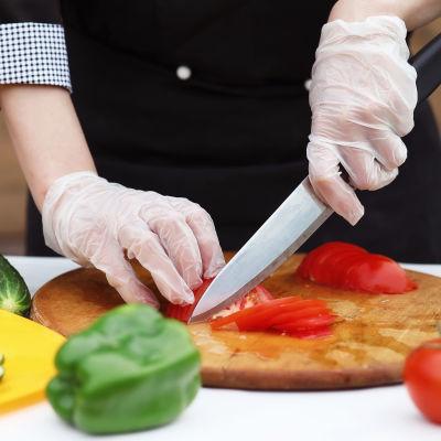 En person skär grönsaker.