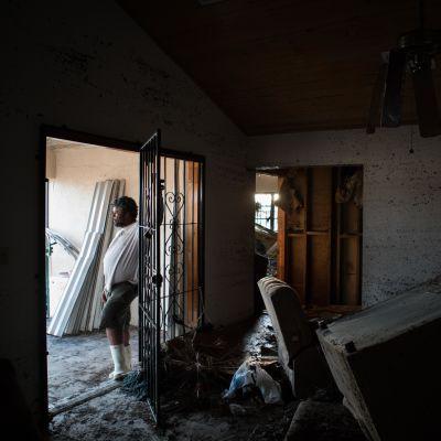 En man står i en dörröppning. Till höger bråte.
