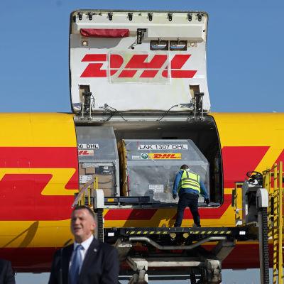 Ett gul-rött flygplan med en öppen lucka på sidan. Inne i lastrummet kan man se några plåtcontainrar.