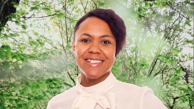 Elina Sagne-Ollikainen småler in i kameran framför en grönskande bakgrund.