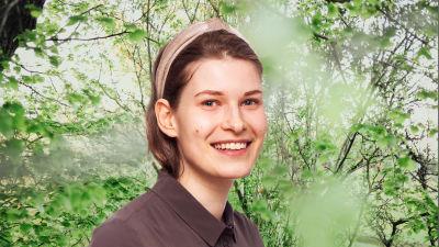 Sara Jakobsén småler in i kameran framför en grönskande bakgrund.