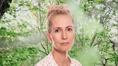 Lina Lehtovaara ser rakt in i kameran. Bakgrunden är en grönskande skogsdunge.