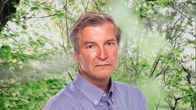 Stefan Lindström ser rakt in i kameran. Bakgrunden är en grönskande skogsdunge.