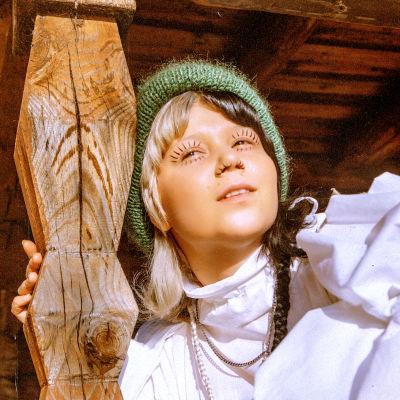 Popmuusikko Vesta puutaustaa vasten.
