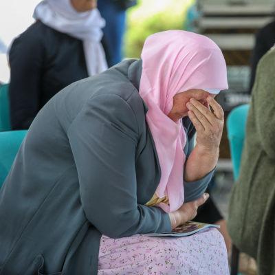 Kyyneliään pyyhkivä nainen.