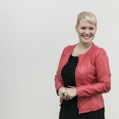 Vaaleahiuksinen nainen hymyilee puolikuvassa, punaisessa jakussa.