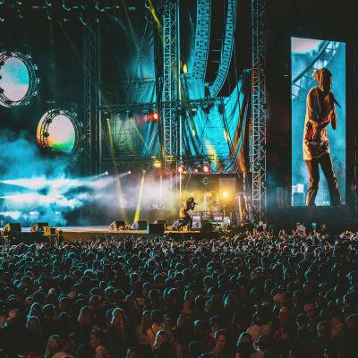 Asap Rocky täyteen ahtautuneen Blockfest-yleisömn edessä lavalla. Kuva on otettu kaukaa, oikean artistin vierellä näkyy hänen kuvansa screenillä moninkertaisena.