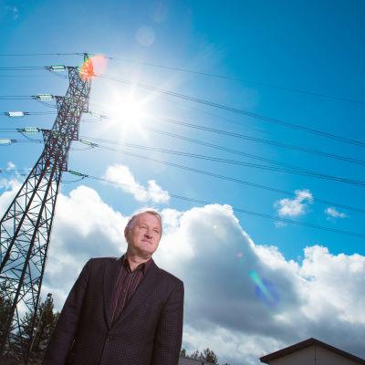 Mies seisoo ulkona sähkölinjan alla.