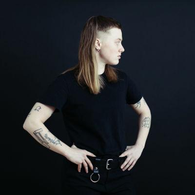 På bilden syns Edith Hammar i profil. Hon tittar åt höger och iklädd svarta kläder och hennes tatuerade armar syns.