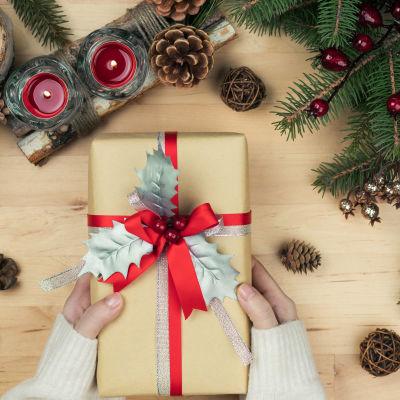 Händer håller i en julklapp paketerat i beige presentpapper och rött och silver band. På bordet finns också dekorerat granris, kottar och röda stearinljus.