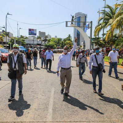 Personer med munskydd går på en asfalterad gata i solskenet, med blå himmel i bakgrunden och en stor, grön palm på sidan av vägen.
