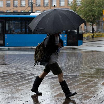 Ihminen kävelee sateella kaupungissa, pää hautautuneena sateenvarjoon.