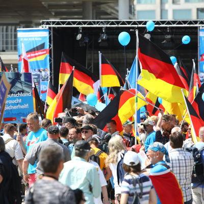 Demonstranter viftar med tyska flaggor under AfD:s demonstration i Berlin i maj 2018.