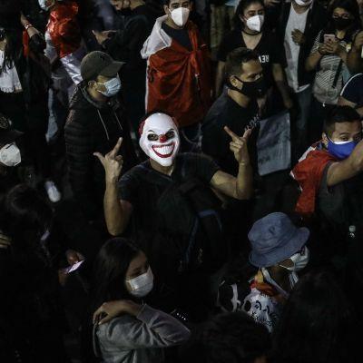 Pellenaamarissa oleva mielenosoittaja näyttää sormimerkkiä protestoijajoukon keskellä.