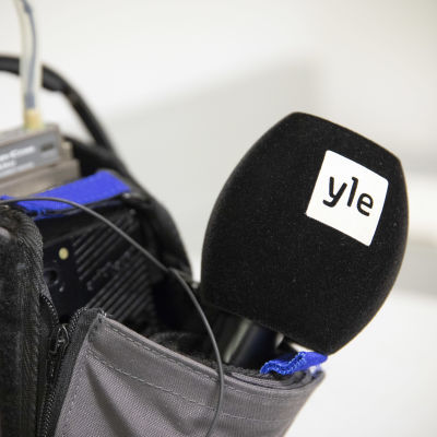 En mikrofon sticker ut ur reporterväskan.