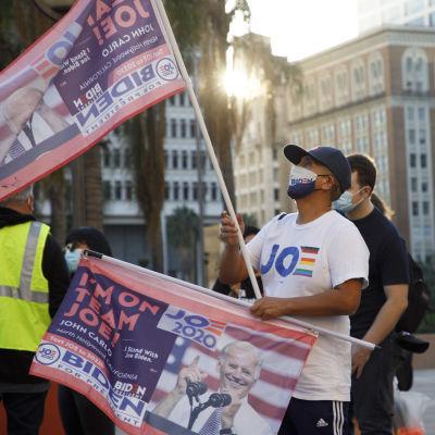Biden-supportrar demonstrerar för full rösträkning i LA i Kalifornien. En man håller upp en Biden-flagga medans solljus sipprar fram mellan byggnader.
