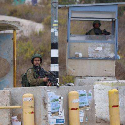 Viiksekäs sotilas seisoo betoniaitauksen takana ase kädessään. Vartiotornissa on toinen sotilas.