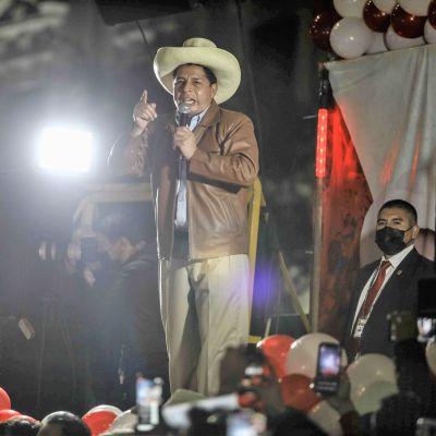 Castillo puhuu lavalla mikrofoniin. Hänellä on ruskea nahkatakki, vaalet housut ja vaalea leveälierinen hattu. Etualalla lavalla näkyy valkoisia ja punaisia ilmapalloja ja lavan edessä yleisöä. Taustalla seisoo mustapukuinen mies maski naamallaan.