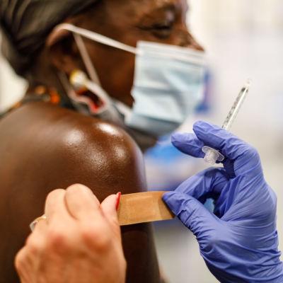 En sjukskötare sätter ett plåster på en persons arm efter vaccinering.