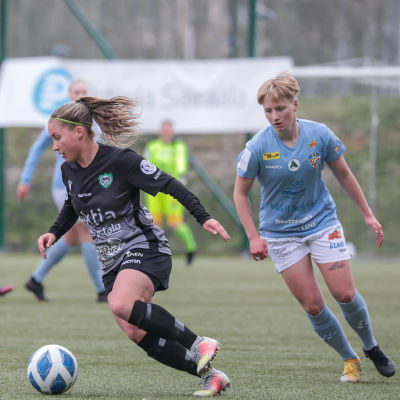Två kvinnliga fotbollsspelare löper på planen. Spelaren klädd i svart har bollen, spelaren i blått följer efter.