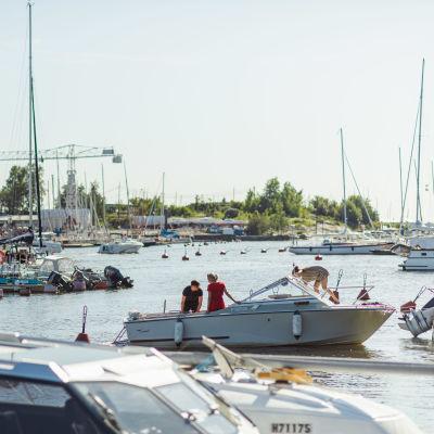 En båthamn med motor- och segelbåtar förtöjda i bryggarna. En motorbåt är i färd att kasta loss.