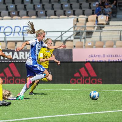 Linda Sällström i blåvitrandig tröja driver med bollen mot KuPS. Hon jagas av KuPS-spelare i gula tröjor. En HJK-spelare har fallit till marken.