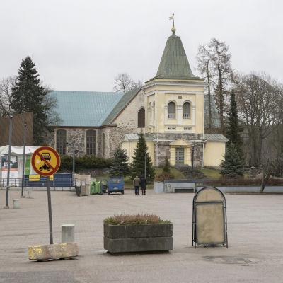 Ett tomt torg, med byggnader, bilar och en kyrka i bakgrunden. Det är mulet och grått väder.
