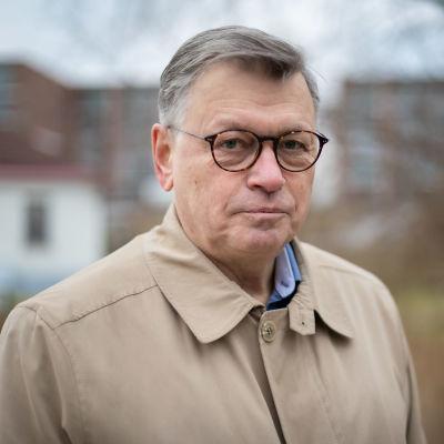 En man i grått hår och glasögon står utomhus. Han har på sig en beige jacka och tittar in i kameran.
