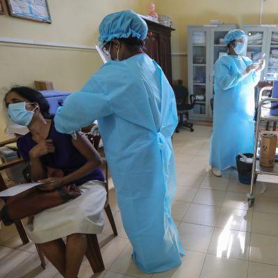 Siniseen suoja-asuun pukeutunut mies piikittää rokotetta tuolilla istuvan naisen käsivarteen. Taustalla toinen mies sinisessä suoja-asussa pitelee rokotepiikkiä ja valkoiseen asuun pukeutunut hotaja tekee jotain hoitotason luona.