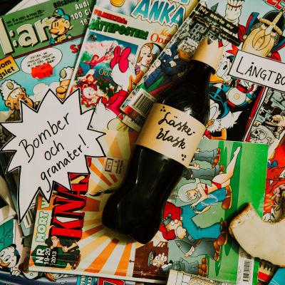 """En hög av serietidningar ligger utspridda. I mitten ligger en svart plasflaska med etiketten """"Läskeblask""""."""