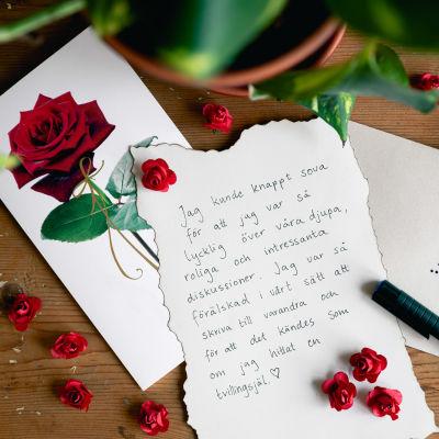 """Ett kärleksbrev skrivet för hand intill ett kuvert adresserat till """"älskling"""" på ett bord med rosor."""