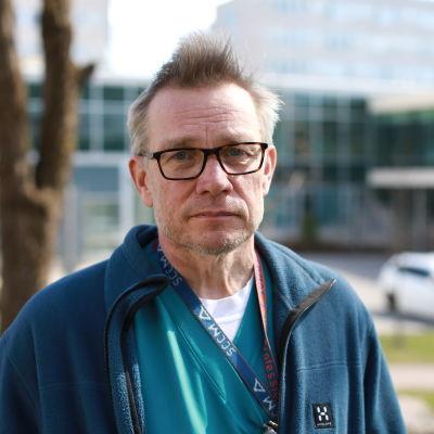 En man i blå jacka, glasögon och kort hår tittar allvarligt in i kameran. Han står utomhus och bakom honom skymtar suddigt en stor vit byggnad med en glasfasad, parkerade bilar och gräsmattor i spirande grönska.