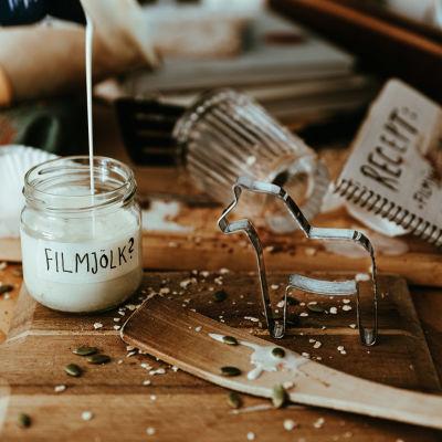 """Ett smutsigt köksbord med en öppen receptbok, en pepparkaksform och en glasburk som fylls av en vit vätska. På burken står det """"filmjölk"""" med frågetecken."""