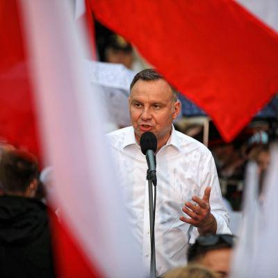 Andrzej Duda puhuu paitahihasillaan mikrofoniin. Etulalalla liehuu Puolan lippuja.