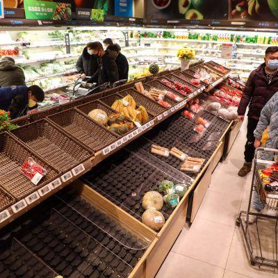 Ansiktsmasker är obligatoriska i Wuhan där folk har hamstrat mat på grund av epidemin