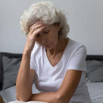 Blond kvinna sitter på sängkanten och håller sig trött för pannan