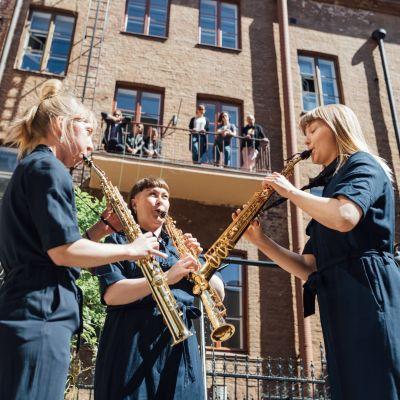 Kolme saksofonistia soittaa helsinkiläisellä sisäpihalla. Kuulijoita seisoo parvekkeella.