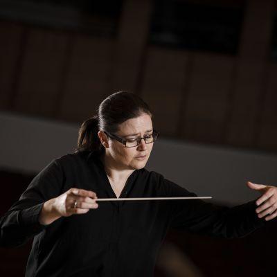 En kvinna i svart som dirigerar.