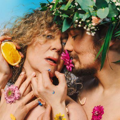 nainen on miehen syleilyssä, miehellä on kukka suussa ja seppele päässä