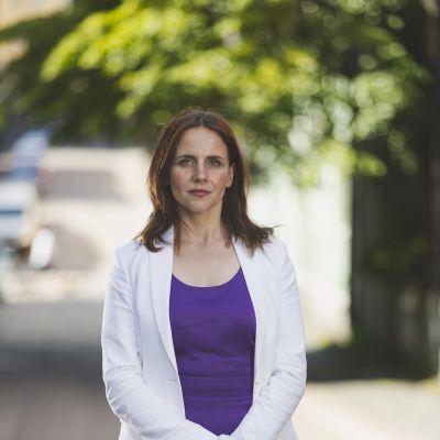 Katariina Säntti direktör inom OP Gruppen står i vit kavaj och lila topp under grönskande träd