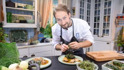 Man ser in i kameran i ett kök och dekorerar en matportion med örter.