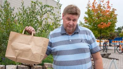 Seppo Elisanen håller upp en papperspåse med gran- och tallplantor i.