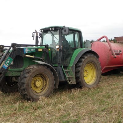 Traktori ja lietevaunu pellolla.
