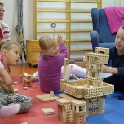 Saksalan päiväkodin lapset Aada, Minttu ja Elmo laittavat palikat järjestykseen lastentarhanopettajan Pirjo Herralan valvonnassa.